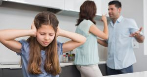 Sad young girl covering ears. Family laws. Steve Morris Law